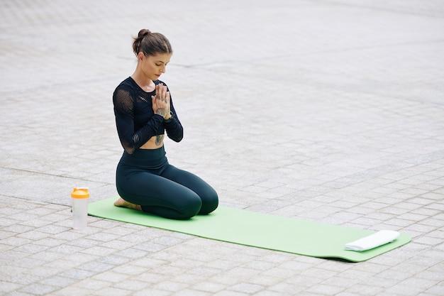 Подходит молодая женщина, размышляя на открытом воздухе на циновке для йоги. она сидит с закрытыми глазами и держит руки в мудре.