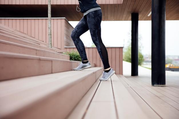 ステップで実行されているフィットの若い女性
