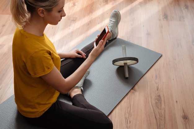 Fit young woman sitting on an exercise mat on floor in her living room and doing workout online with a smartphone