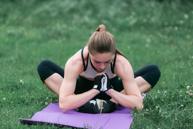Fit young woman in sportswear performs stretching after a work-out outside