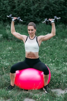 Fit young woman in sportswear uses fitness ball for exercises wo