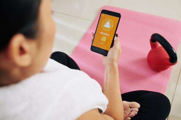 Молодая женщина начинает пятиминутное занятие йогой на смартфоне, чтобы потренироваться дома