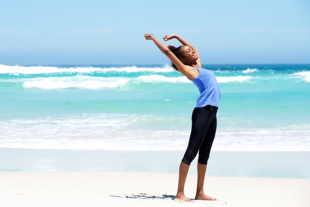 Fit young woman stretching at beach
