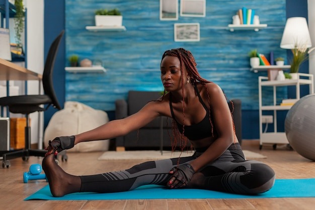 Fit young woman stretching reaching toes sitting on yoga mat after intense workout in home with dumbbells training