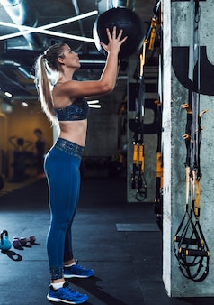 Fit young woman throwing medicine ball in gym
