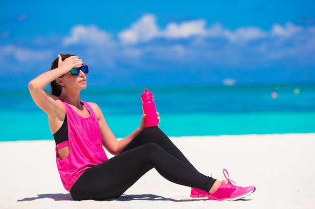 Fit young woman on tropical white beach in her sportswear