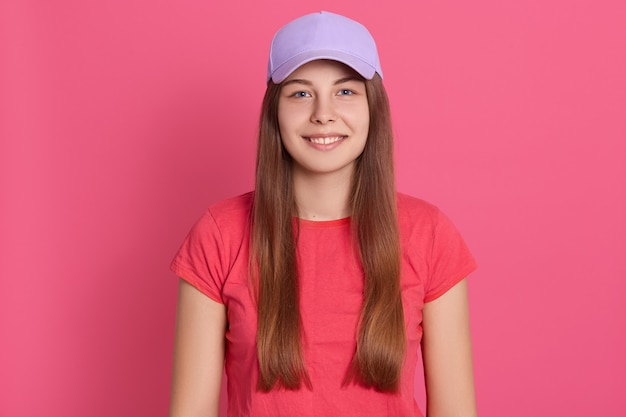 Fit young woman wearing casual t shirt standing isolated over rosy wall . beautiful model in baseball cap
