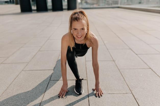 実行の準備をしてスポーツユニフォームを着ている若い女性に合います。全力疾走する健康な若い白人女性の全身ショット。