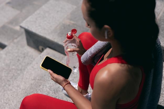 赤いスポーツウェアと白いイヤホンで黒髪の若い女性をフィットさせるスマートフォンと水筒を保持します。ハイアングルカットビュー。バイオレットタオルが彼女の肩に掛かっています。大都市のコンセプトでスポーツ。