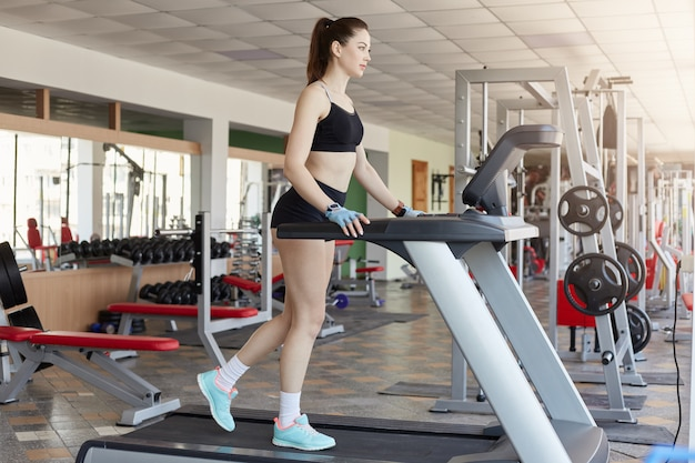 Fit young woman with ponytail being in action running on treadmill, female with beautiful legs exercising on treadmill at gym, lady wearing black sporty wear, girl likes fitness.