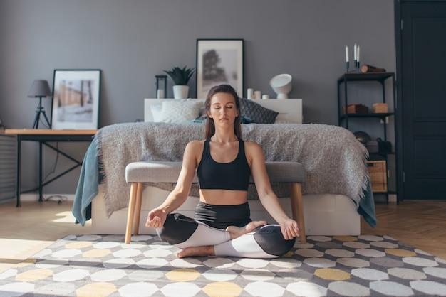 집에서 운동, 요가 운동을하는 젊은 여성을 맞추고, 그녀는 이완하고 진정됩니다.