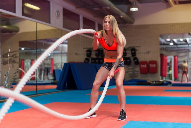 ジムでバトルロープでワークアウトの若い女性に合います。