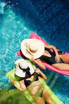 호텔 수영장에서 떠 있는 매트리스에서 일광욕을 할 때 밀짚 모자로 얼굴을 덮는 젊은 여성을 맞추십시오.