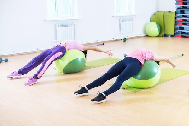 Подходят молодые женщины, растягивающие спину лежа на фитнес-мячах.