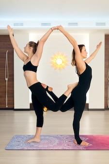 Пара женщин в тренажерном зале делают упражнения на растяжку йоги. fit и велнес образ жизни.