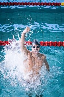 Fit человек, торжествующий с кулаком в бассейне