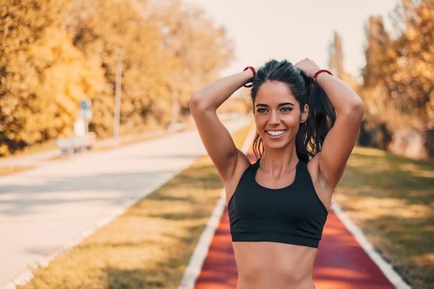 Fit спортсменка, связывая волосы перед ее тренировки на открытом воздухе на беговой дорожки.