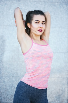 Fit фитнес женщина делает упражнения на растяжку на открытом воздухе