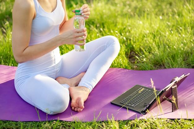 Fit женщина занимается йогой и смотреть онлайн-учебники на смартфоне