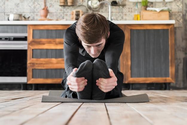 Fit мужчина растягивает ноги на коврике