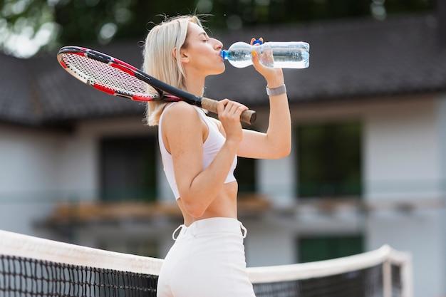 Fit девушка с теннисной ракеткой пить