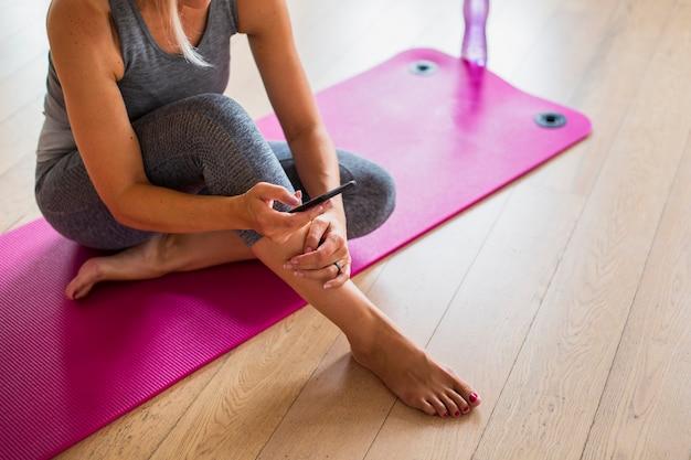 Fit девушка сидит на коврик для йоги с телефоном