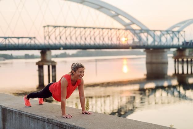 Fit спортивный милая блондинка делает отжимания возле реки рано утром.