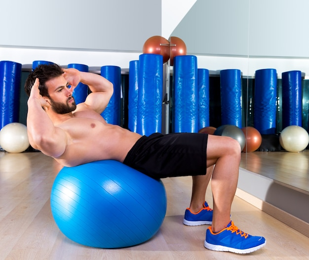 Fitball abdominal crunch swiss ball man at gym