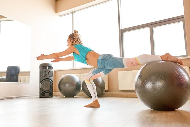 Женщина делая тренировки с fitball в классе спортзала фитнеса. вовлечение основных мышц живота. концепция изображения здорового образа жизни для женщин.