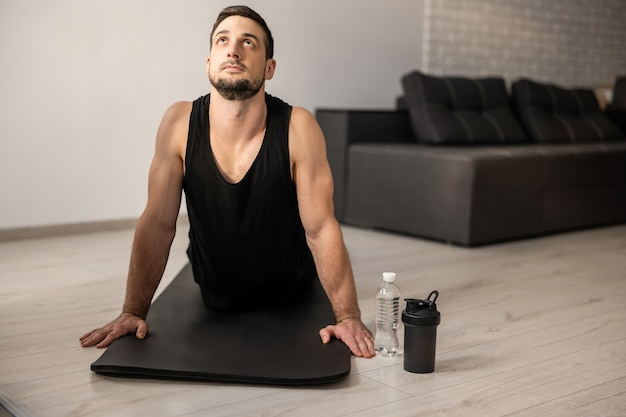 Fitn man meditating while doing cobra pose in living room. indoor shot of handsome young man practicing yoga. morning workout. black sportswear. plastic water bottle. strong arms.