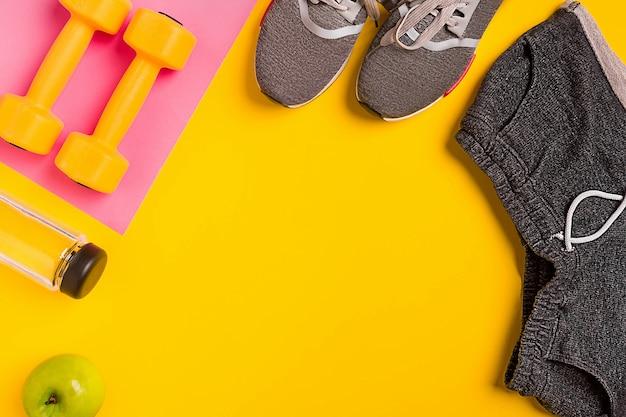 黄色の背景にフィットネスアクセサリー。スニーカー、水のボトル、リンゴ、ダンベル。静物