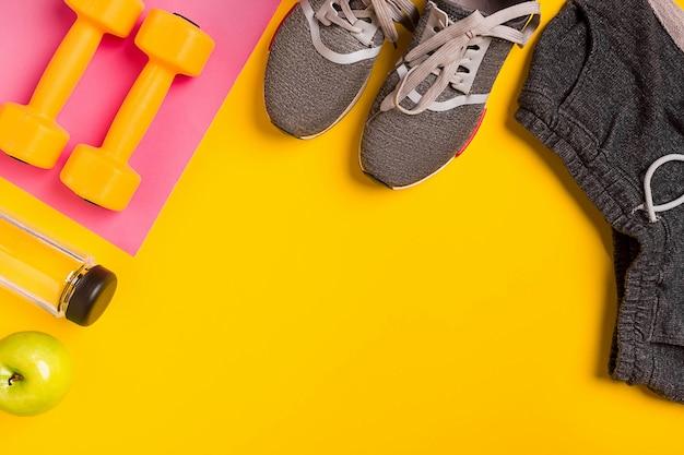 Фитнес аксессуары на желтом фоне кроссовки бутылка воды и гантели
