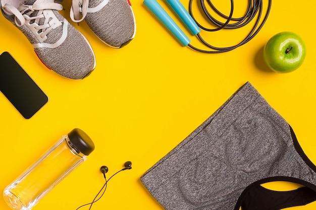 ウォーターヘッドホンとスポーツトップの黄色の背景スニーカーボトルのフィットネスアクセサリー