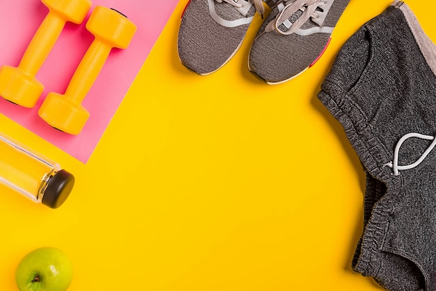 Fitness accessories on a yellow background. sneakers, bottle of water, apple and dumbbells. still life
