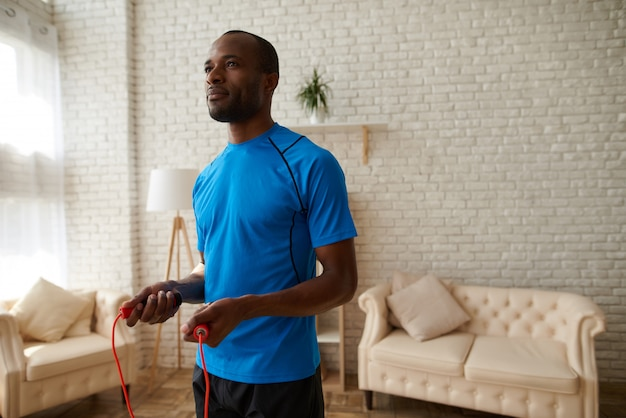 Fitness african athlete doing exercises with jumping rope.