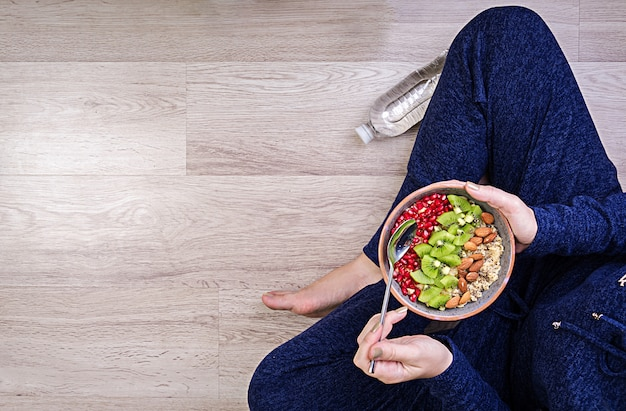 Фитнес и концепция здорового образа жизни. женщина отдыхает и ест здоровую овсянку после тренировки. вид сверху.