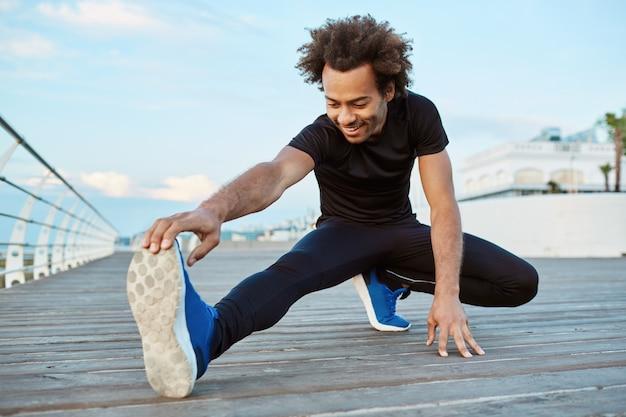 체력과 동기 부여. 아침에 부두에서 스트레칭하는 즐겁고 웃는 어두운 피부 운동 선수. 그의 다리를 따뜻하게하는 덥수룩 한 머리카락을 가진 스포티 한 아프리카 계 미국인 남성