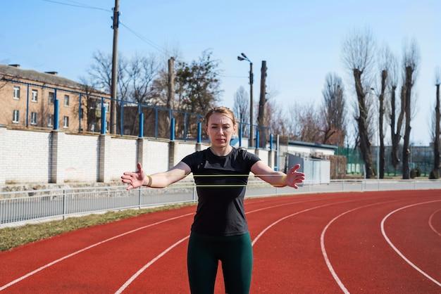 フィットネスとスポーツのコンセプト、屋外トレーニング。スポーツスタジアムで屋外に立っている輪ゴムで手のフィットネスを訓練するフィットネスの女の子