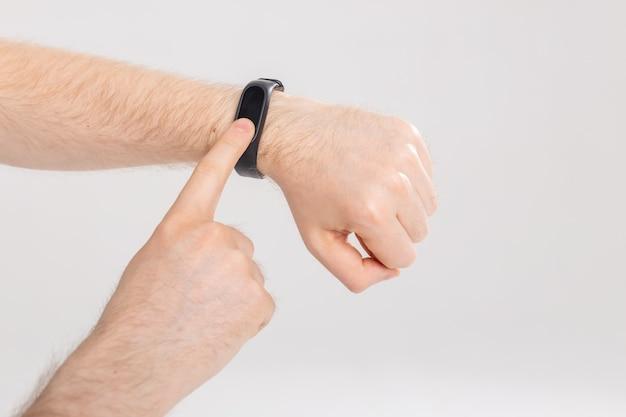 Концепция фитнеса и технологии - трекер активности на мужском запястье на белой стене с копией пространства.