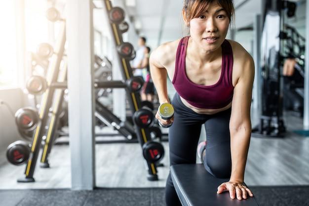 Гантель азиатской девушки фитнеса поднимаясь на спортзале.