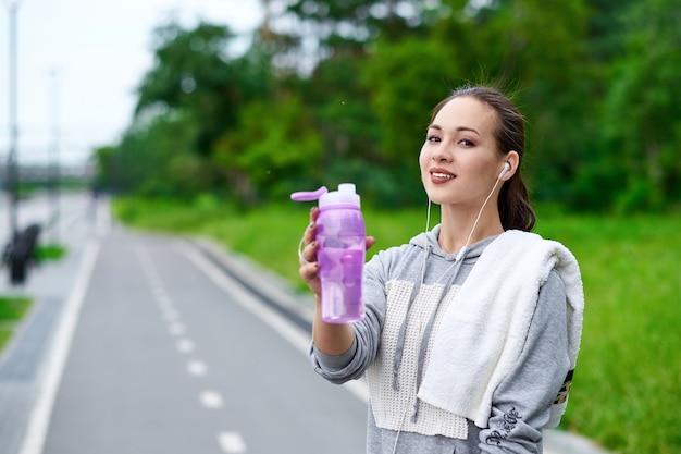 夏の公園でトレーニングをした後、水のボトルとタオルを持つフィットネス アジア人女性