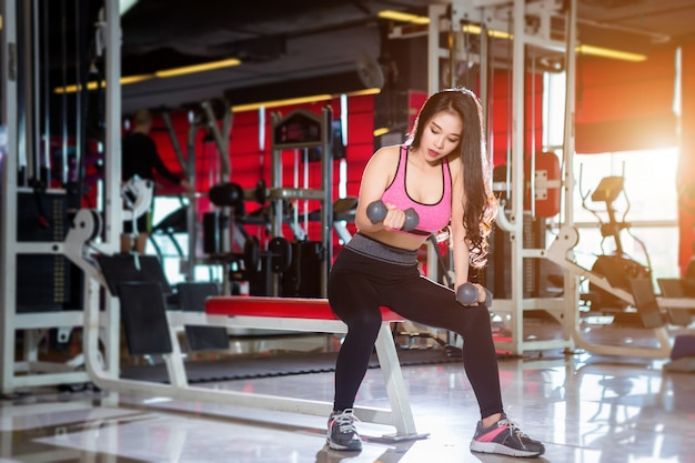 Fitness asian women performing doing exercises training with dumbbell sport in  gym backgr
