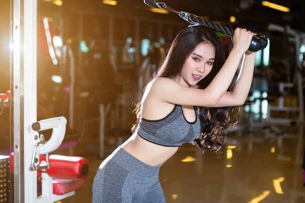 Fitness asian women performing doing exercises training with rowing machine (seat cable rows machine)