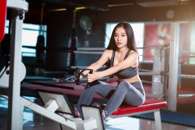 Fitness asian women performing doing exercises training with rowing machine in sport gym