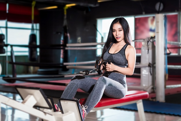 Fitness asian women performing doing exercises training with rowing machine