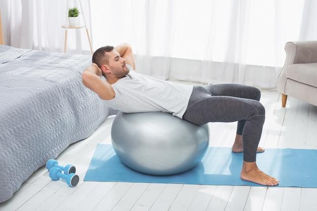 Фитнес дома. красивый привлекательный мужчина делает упражнение, лежа на медицинском мяче