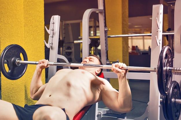 Фитнес, спортсмен, бодибилдинг и люди концепции - мышечная тренировка жима лежа культуриста.