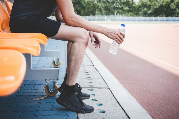 Fitness athlete man resting on bench with bottle of water preparing to running on road track