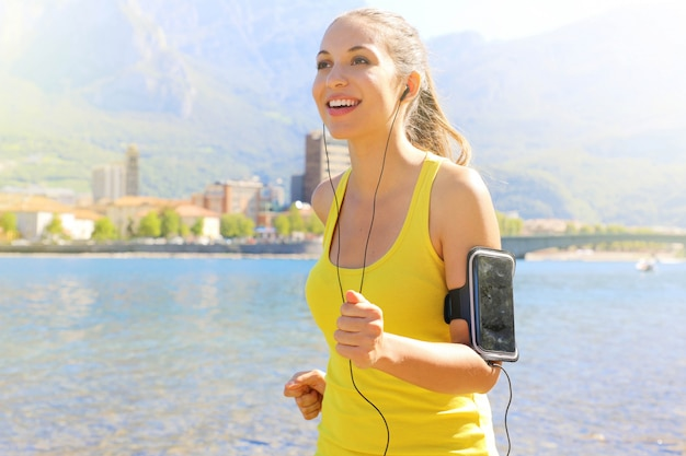 Fitness athlete woman running and wearing phone armband with touchscreen during cardio workout on lake.