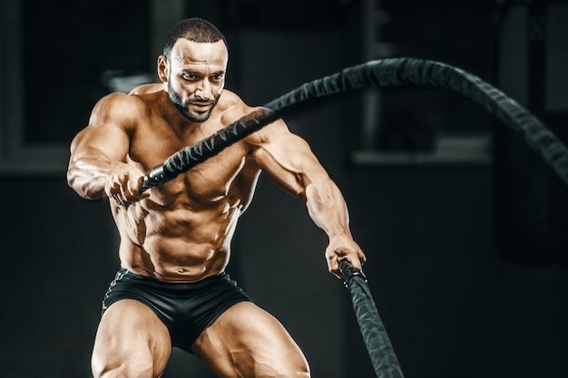 Fitness athletes training using battle ropes